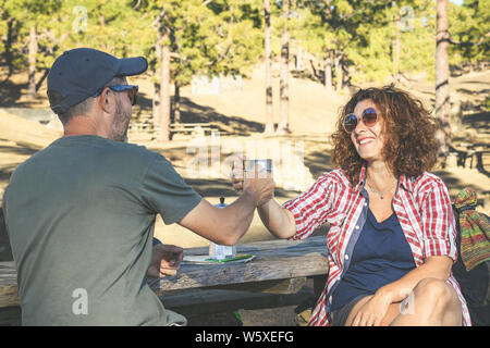 Smiling couple toast with coffee in the mugs sitting in the park. Trendy happy husband and wife drinking and relaxing after mountain trekking. Togethe - Stock Photo