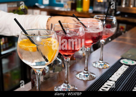 Doncaster, UK - May 11 2019: Cocktail glasses lined up on the bar as the waitress mixes drinks at La Boca  restaurant & steakhouse, 1 Netherhall Road - Stock Photo