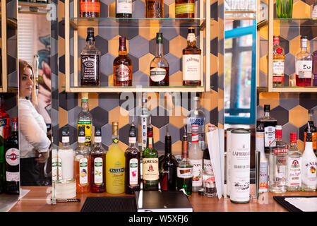 Doncaster, UK - May 11 2019: Waitress reflected in mirror behind the bar with bottles f alcohol on display at La Boca  restaurant & steakhouse, 1 Neth - Stock Photo