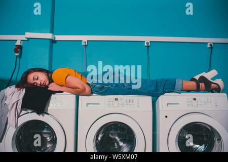 Young woman searching clothes in washing machine drum at laundromat. - Stock Photo