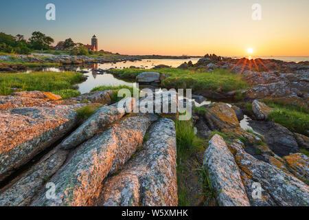 Svaneke Gamle Fyr lighthouse and rocky coastline along east coast at sunrise, Svaneke, Bornholm Island, Baltic sea, Denmark, Europe - Stock Photo