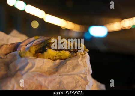 Driver at night eating an egg, sausage, and cheese croissant. - Stock Photo