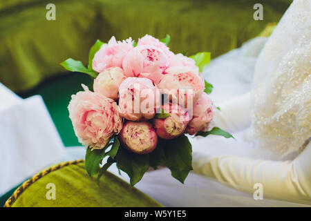 a bride in a lace wedding dress is holding a wedding bouquet of light flowers - there are roses, orchids in the bouquet. - Stock Photo