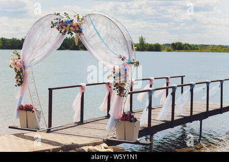 Part of the wedding arch decorated with fresh flowers is set on the sandy bank of the river. Wedding florist arranges workflow. - Stock Photo