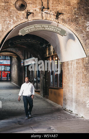 London, UK - July 23, 2019: Man walking under 'Thank you for visiting' sign above the exit from Borough Market, one of the largest and oldest food mar - Stock Photo