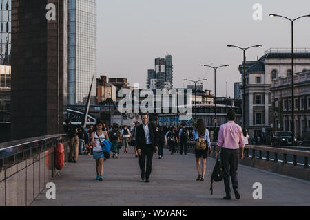 London, UK - July 23, 2019: People walking on London Bridge during blue hour, selective focus, city on the background. London is one of the most visit - Stock Photo