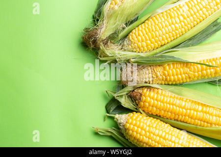 Fresh Grains of ripe corn, corn cob  over green background - Stock Photo