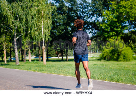 Young athletic man jogging in the park - Stock Photo