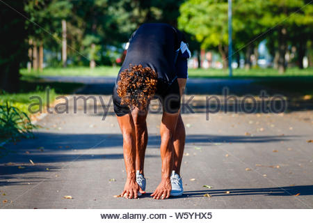 Young mixed race sportsman doing exercises in the park - Stock Photo