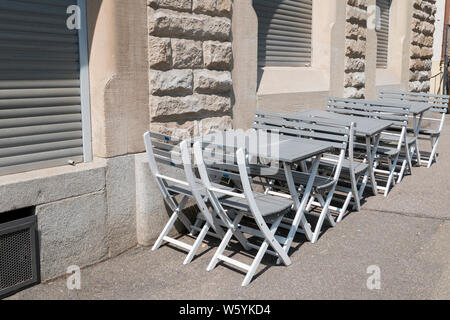 empty chairs and tables in front of a restaurant - Stock Photo