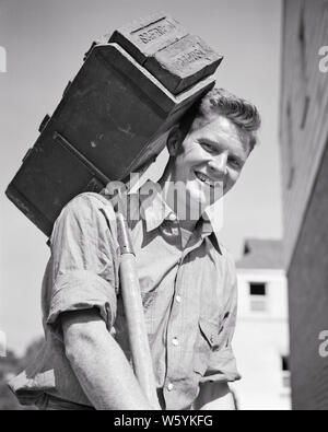 1940s SMILING MAN CONSTRUCTION WORKMAN MASON LOOKING AT CAMERA AT HOUSE BUILDING SITE CARRYING A HOD FULL OF BRICKS - b18748 HAR001 HARS 1 FITNESS FACIAL MORTAR CAREER HEALTHY YOUNG ADULT BALANCE SAFETY STRONG WORKMAN PLEASED JOY LIFESTYLE HOUSES JOBS SITE BRICKS HALF-LENGTH PHYSICAL FITNESS PERSONS RESIDENTIAL MALES RISK BUILDINGS PROFESSION CONFIDENCE EXPRESSIONS B&W EYE CONTACT SKILL ACTIVITY MATERIAL OCCUPATION HAPPINESS PHYSICAL SKILLS CHEERFUL STRENGTH CAREERS LOW ANGLE PRIDE MASON A AT OF HOMES OCCUPATIONS SMILES CONCEPTUAL FLEXIBILITY JOYFUL MUSCLES RESIDENCE OR MID-ADULT MID-ADULT MAN - Stock Photo