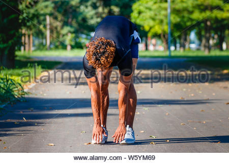 Young athletic man exercising in the park - Stock Photo
