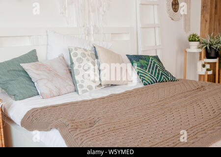 Green, beige pillow on bed in bedroom with pastel colored bedsheets on bed. stylish white apartment design in lagom style.Stylish scandinavian white