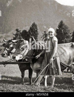 1920s 1930s SMILING WOMAN IN NATIONAL DRESS LOOKING AT CAMERA LEADING TWO COWS HARNESSED TO WAGON IN THE ALPS BAVARIA GERMANY - c6748 HAR001 HARS PLEASED JOY LIFESTYLE FEMALES JOBS RURAL HEALTHINESS HOME LIFE DAIRY NATIONAL LADIES PHYSICAL FITNESS COW GERMANY PERSONS CARING FARMING CONFIDENCE LEADING AGRICULTURE B&W HORNS CATTLE SKILL OCCUPATION HAPPINESS SKILLS CHEERFUL STRENGTH FARMERS POWERFUL COWS PRIDE IN THE TO OCCUPATIONS SMILES BAVARIA BAVARIAN ALPS JOYFUL SMOCK STYLISH HARNESSED MAMMAL YOUNG ADULT MAN BLACK AND WHITE CAUCASIAN ETHNICITY DOMESTICATED HAR001 LIVESTOCK OLD FASHIONED - Stock Photo