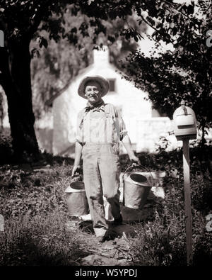 1920s 1930s SMILING MAN DAIRY FARMER WEARING STRAW HAT AND OVERALLS WALKING TOWARD LOOKING AT CAMERA CARRYING TWO MILKING PAILS - d3761 HAR001 HARS OLD FASHION 1 FITNESS FACIAL STYLE CAREER HEALTHY BALANCE PLEASED JOY LIFESTYLE JOBS RURAL HEALTHINESS DAIRY COPY SPACE FULL-LENGTH PERSONS OVERALLS FARMING MALES PROFESSION CONFIDENCE EXPRESSIONS AGRICULTURE B&W EYE CONTACT FREEDOM SUCCESS SKILL ACTIVITY OCCUPATION HAPPINESS PHYSICAL SKILLS CHEERFUL STRENGTH AND MILKING CAREERS FARMERS TOWARD PAILS PRIDE OCCUPATIONS SMILES CONCEPTUAL STRAW HAT FLEXIBILITY JOYFUL MUSCLES STYLISH MID-ADULT - Stock Photo