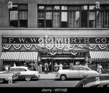1950s STORE FRONT WOOLWORTH DEPARTMENT STORE NEW YORK CITY DECORATED BUNTING FOR SPECIAL SALE  42nd STREET WEST OF 5TH AVE  - q55259 CPC001 HARS BUILDINGS DECORATED TRANSPORTATION B&W NORTH AMERICA SHOPPER SUMMERTIME NORTH AMERICAN SHOPPERS MIDTOWN PROPERTY CUSTOMER SERVICE AUTOS 5TH EXTERIOR SPECIAL PRIDE OPPORTUNITY WOOLWORTH BUNTING NYC STORES AWNINGS REAL ESTATE NEW YORK STRUCTURES AUTOMOBILES CITIES PATRIOTIC STOREFRONT VEHICLES AVE EDIFICE NEW YORK CITY BRANDING BRAND NAME COMMERCE WOOLWORTH'S 42ND 42ND STREET 5 AND 10 5 AND DIME BLACK AND WHITE BUSINESSES OLD FASHIONED - Stock Photo