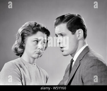 1960s young couple looking at one another with angry mad facial expressions - s13057 HAR001 HARS OLD FASHION 1 FACIAL ANGER COMMUNICATION YOUNG ADULT SAFETY LIFESTYLE ANNOYED FEMALES MARRIED STUDIO SHOT MOODY SPOUSE HUSBANDS HOME LIFE COPY SPACE FRIENDSHIP HALF-LENGTH LADIES MARRIAGE PERSONS CARING MALES EXPRESSIONS TROUBLED B&W PARTNER SADNESS SUIT AND TIE DISAGREEING DISTRESSED POUTING IRATE DISAGREEMENT HURTFUL AT DISAGREE HURT MOOD CONNECTION CONCEPTUAL GLUM SPAT STYLISH DISPLEASURE HOSTILITY NEWLYWED PETULANT ANNOYANCE ANOTHER EMOTION EMOTIONAL IRRITATED MISERABLE QUARREL SQUABBLE WIVES - Stock Photo