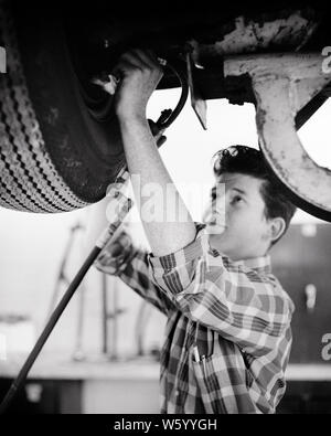 1950s 1960s TEEN BOY WORKING ON CAR IN AUTOMOTIVE  MECHANICS HIGH SCHOOL CLASS - s16043 HAR001 HARS PERSONS AUTOMOBILE MALES TEENAGE BOY CONFIDENCE TRANSPORTATION B&W GOALS SCHOOLS AUTOS HAIRSTYLE KNOWLEDGE LOW ANGLE MECHANICS PRIDE OPPORTUNITY AUTOMOTIVE HIGH SCHOOL OCCUPATIONS HIGH SCHOOLS CONNECTION AUTOMOBILES STYLISH TEENAGED VEHICLES VOCATION COOPERATION GROWTH JUVENILES TECHNICAL VO-TECH VOCATIONAL BLACK AND WHITE CAUCASIAN ETHNICITY HAR001 OLD FASHIONED - Stock Photo