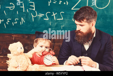 Individual lesson concept. Boy, child on calm face holds alarm clock while teacher talk to kid. Teacher with beard, father teaches little son in classroom, chalkboard on background. - Stock Photo