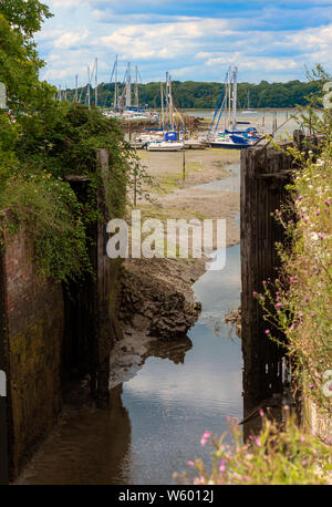 Chichester Canal Lock Gates in summer looking towards Birdham Pool Marina at low tide, Chichester Harbour, West Sussex, England, United Kingdom - Stock Photo