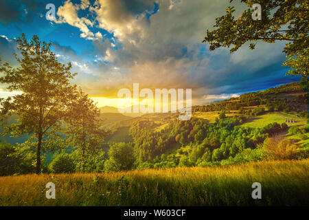 Colorful sunset over the green hills landscape - Stock Photo