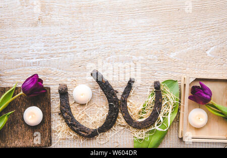Flat lay view of two rusty small and big horseshoes on light wooden board background, decorated with white small candles and purple tulips, spring in - Stock Photo
