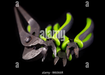 Pliers and pliers on a workshop table. Accessories for mechanic and hudraulics. Dark background. - Stock Photo