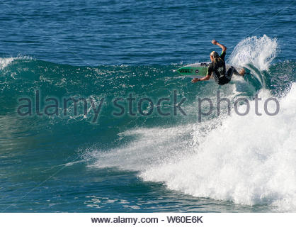 A male surfer performing a frontside slashing top-turn on a glassy-wave, during ideal surf conditions at Iluka; on Australia's Pacific coast. - Stock Photo