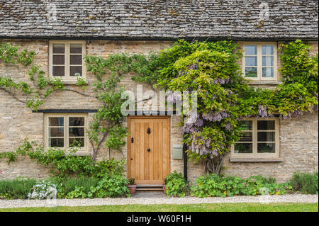 Narrow lane with romantic thatched houses and stone cottages in the lovely Minster Lovell village, Cotswolds, Oxfordshire, England - Stock Photo