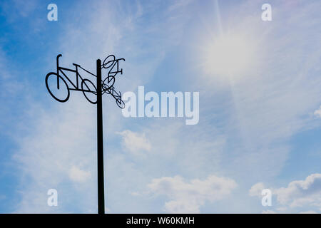 Sculpture with bicycle silhouettes hanging on a pole, with sky and sun in the background, to indicate to cyclists the route to follow. - Stock Photo