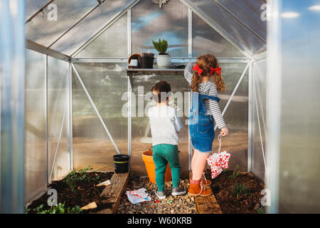 Young boy and girl checking on greenhouse in back yard