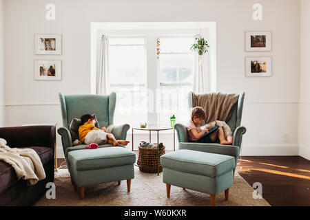 Young boy and girl resting in living room using tablets - Stock Photo