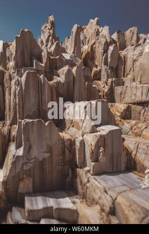 A beautiful vertical shot of rock formations in a desert with blue sky in the background - Stock Photo