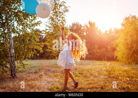 Happy little girl running with baloons in hand. Kid having fun in summer park at sunset. Stock Photo