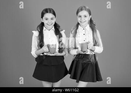 A very good morning to you. Little children drinking morning tea or coffee. Cute schoolgirls holding tea cups. School children having breakfast in morning. Small girls enjoying their school breakfast. - Stock Photo