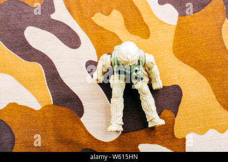 Soldier figurine on a camo background in the view - Stock Photo