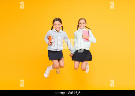 Happy to be back to school. Elementary school pupils in mid air. Little girls jumping with books on yellow background. Small kids enjoying school break time. Welcome the children to school. - Stock Photo