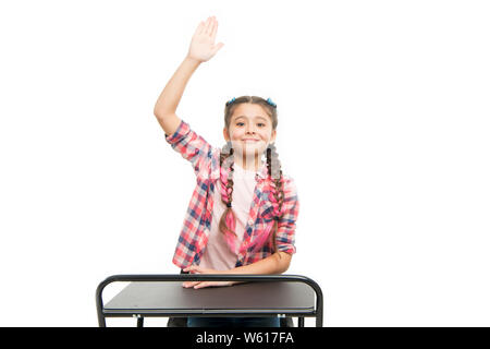 Ready for back to school. Little schoolgirl recitig lesson in primary school. Cute child raising hand at school desk isolated on white. Adorable small girl enjoying her school time. - Stock Photo