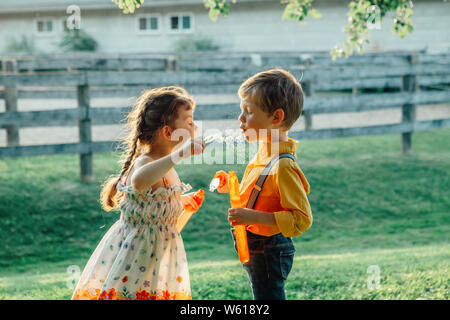Funny Caucasian children girl and boy blowing soap bubbles in park at summer sunset. Real authentic happy childhood moment of friendship. Lifestyle ac