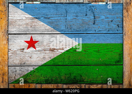 National flag of Djibouti on a wooden wall background.The concept of national pride and symbol of the country.Flag painted on a wooden fence with meta - Stock Photo