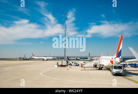 PARIS, FRANCE-MARCH 30, 2019 : Aircraft of Airfrance airline docking at Paris Charles de Gaulle airport. Air France airplane with blue sky and white - Stock Photo