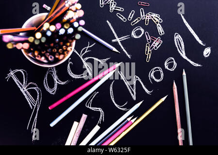 Back to school hand written on black background, among pencils and other student supplies. - Stock Photo