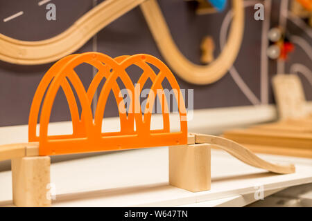 Wooden toy train, bridge. miniature railroad bridge. The black engine pulling colorful cars on the floor. Educational toys for children in preschool - Stock Photo