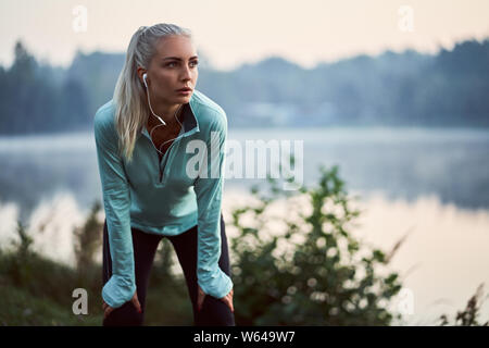 Female jogger listen to music while having rest during early morning exercise - Stock Photo