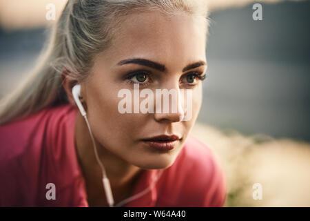 Closeup of female runner wearing earphones - Stock Photo