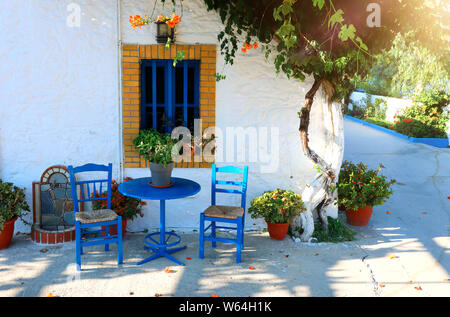 landmark photo of blue chairs with table in typical Greek town - Stock Photo