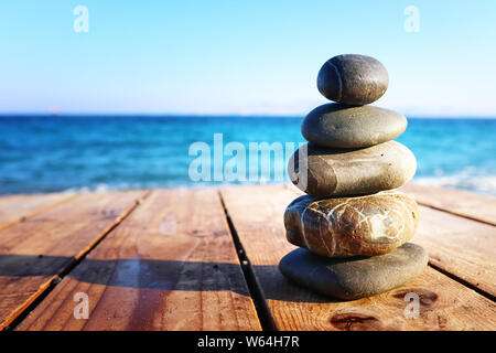Stones pyramid on over beach wooden deck symbolizing harmony, zen and balance - Stock Photo