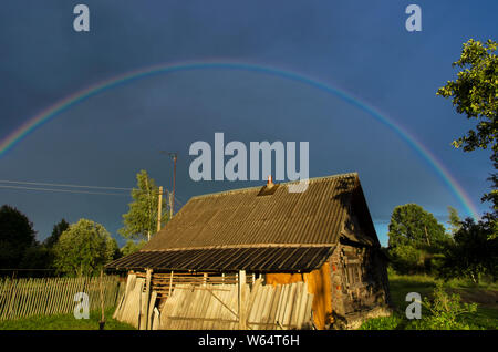 Rainbow in the dramatic sky over an old boarded-up log house in the countryside - Stock Photo