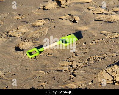 A child's plastic spade lies abandoned on the yellow sand of a Norfolk Beach adding to the plastics pollution of our seas.