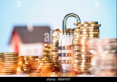 Combination lock with several stacks of coins and house in the background - Stock Photo
